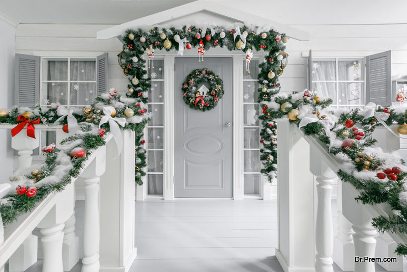 Minimalistic idea Are you tired of all the bright lights and decorations around? Go in for the minimalistic look by hanging three wreaths neatly aligned on the door and just two evergreen planters on both sides. The calm and relaxed look might be just what is right for you this season, and one of the classy porch decoration ideas for your outdoors. Add neutral colors to establish the serene beauty.