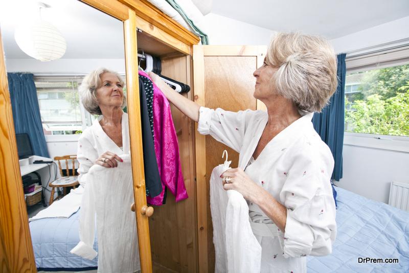 Senior woman choosing dress from closet